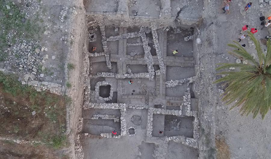Overhead shot of an archaeological dig at a site known as Megiddo, stone walls bounding several rooms are shown.