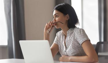 Woman holding glasses to mouth, gazing over laptop.